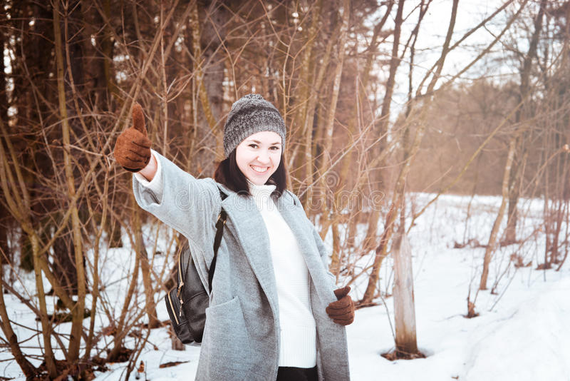 Portrait of a happy beautiful girl with brown hair in the winter forest dressed in a hipster style, lifestyle stock photography