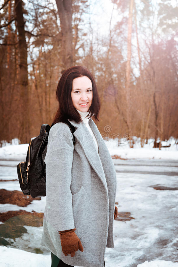 Portrait of a happy beautiful girl with brown hair in the winter forest dressed in a hipster style, lifestyle stock photos