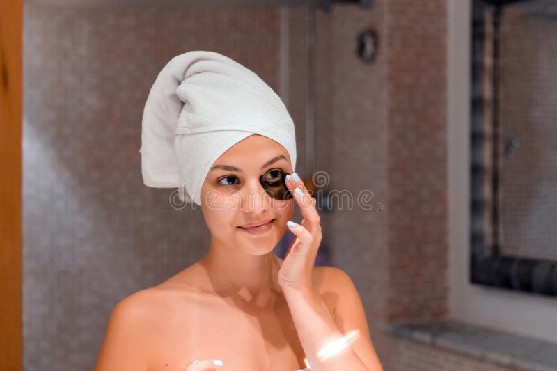 Portrait of happy beautiful girl putting on patches under eyes in bathroom. Beauty skincare and wellness morning concept stock photos