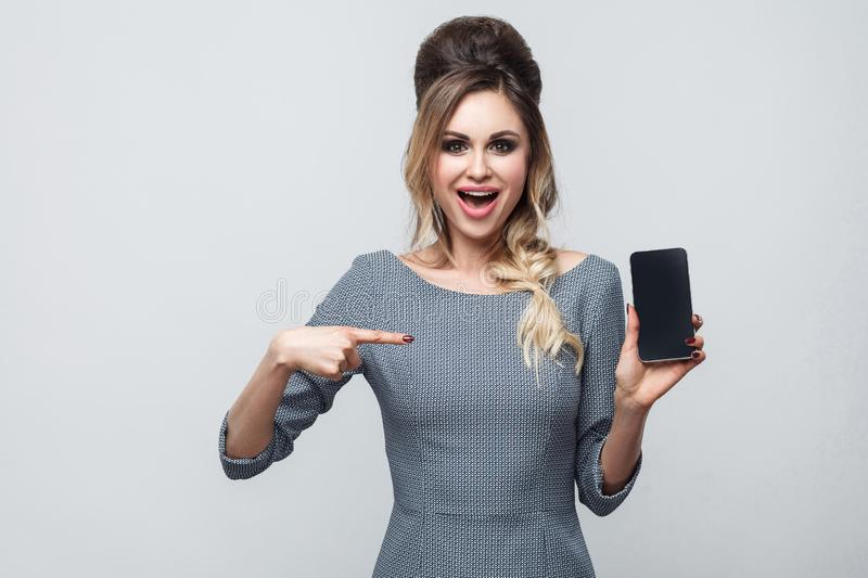 Portrait of happy beautiful modern young girl in grey dress standing, holding and pointing finger to cell phone and toothy smile,. Looking at camera. Indoor royalty free stock photography