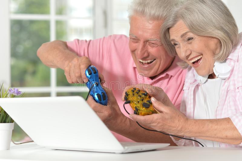 Portrait of happy beautiful senior couple playing computer game stock photo