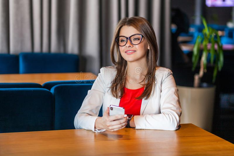 Portrait of happy beautiful stylish brunette young woman in glasses sitting with mobile smart phone and looking away with toothy stock photography