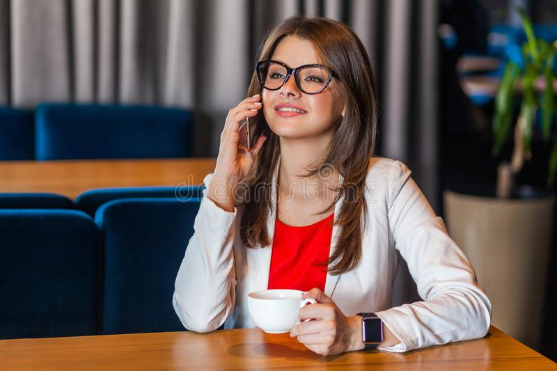Portrait of happy beautiful stylish brunette young woman in glasses sitting talking on mobile smart phone and toothy smile stock image