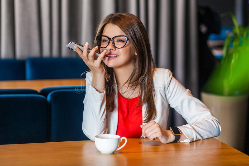 Portrait of happy beautiful stylish brunette young woman in glasses sitting, toothy smile, holding her mobile smart phone and stock images