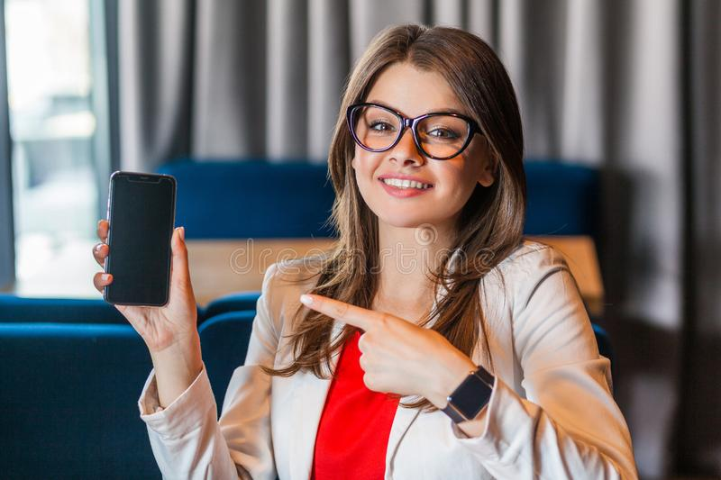 Portrait of happy beautiful stylish young woman in glasses sitting, showing and pointing at mobile smart phone screen and looking stock images