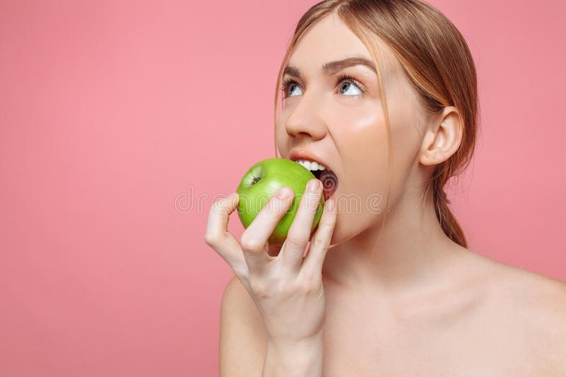 Portrait of a happy beautiful woman holding an apple trying to bite him, with healthy teeth on a pink background. Natural beauty concept royalty free stock photo