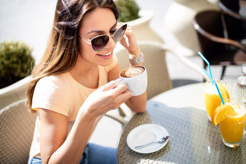 Portrait of happy young woman holding coffee in cafe outdoor stock image