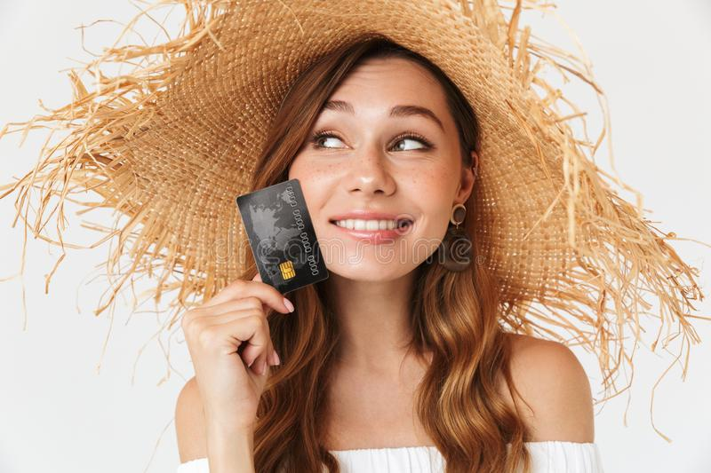 Portrait of happy beautiful woman 20s wearing big straw hat smiling and holding credit card near face, isolated over white stock image