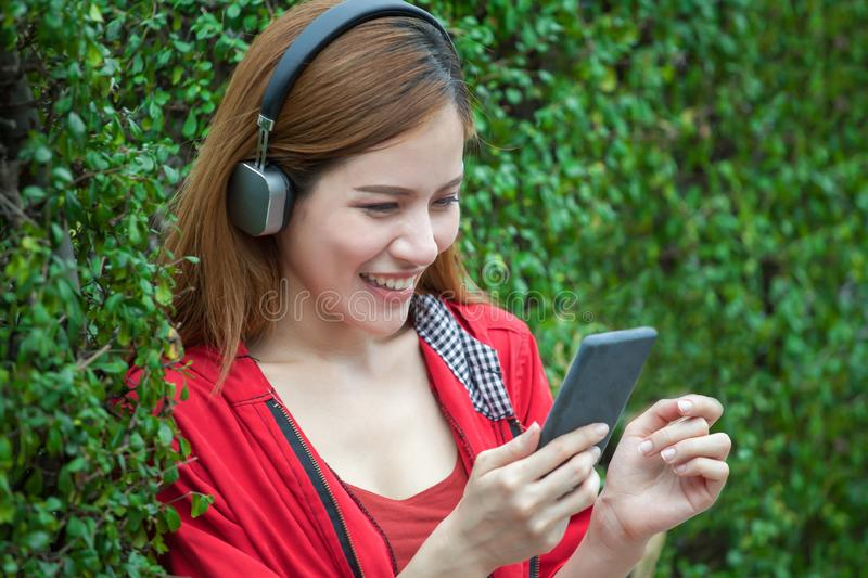 portrait of happy beautiful Young Asian women smiling in red coat listening wireless music enjoy with headphones from a smart stock image