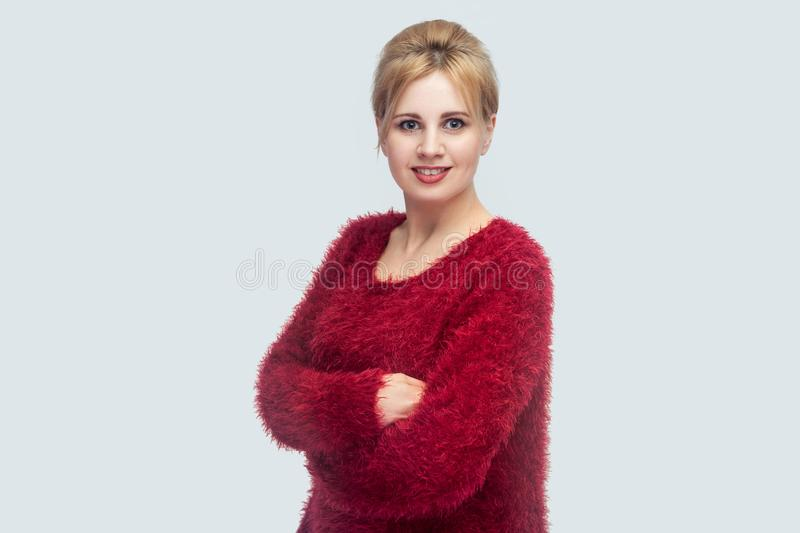 Portrait of happy beautiful young blond woman with makeup and bun hair, red blouse standing, crossed arms and looking at camera stock photos