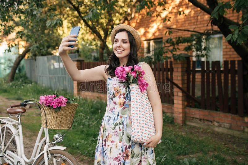 Portrait of a happy beautiful young girl with vintage bicycle and flowers doing selfie. Bike with basket full of pink stock image