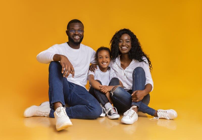 Portrait of happy black family smiling over yellow studio background stock photos