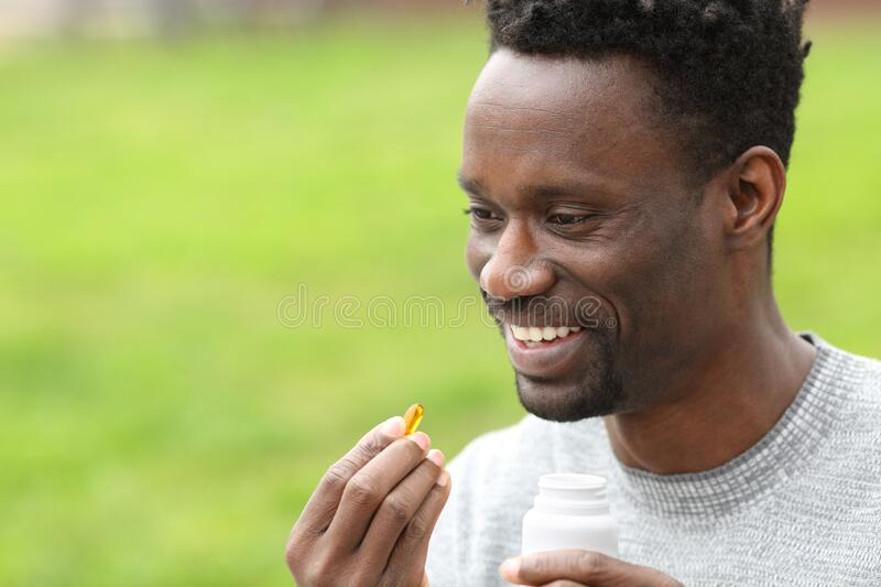 Happy black man taking vitamin pill in the park. Portrait of a happy black man taking vitamin omega3 pill in the park royalty free stock images