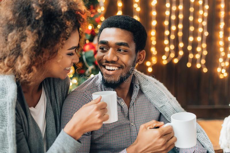 Young couple drinking coffee at Christmas tree stock images