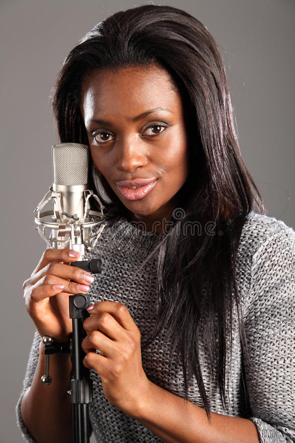 Portrait happy black woman singer in music studio royalty free stock image