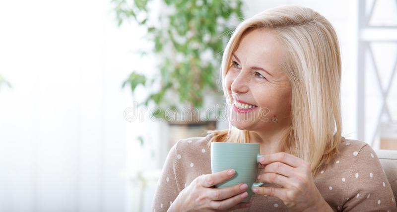 Portrait of happy blonde with mug in hands stock photo