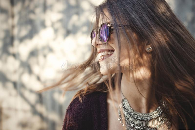 Portrait of happy boho girl in cool outfit and sunglasses smiling in sunny street. Stylish hipster carefree girl posing on stock photos