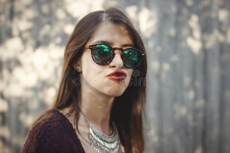 Portrait of happy boho girl in sunglasses having fun and smiling in sunny street. Stylish hipster carefree girl posing on stock photography