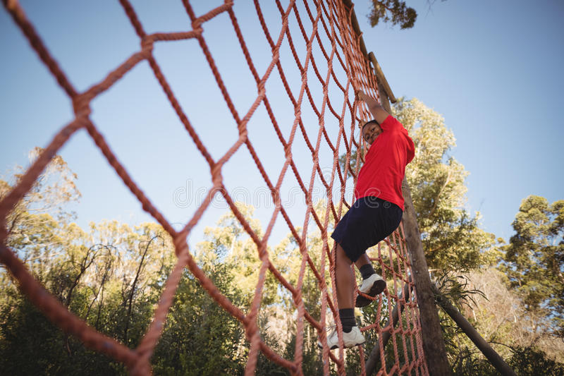 Portrait of happy boy climbing a net during obstacle course royalty free stock photo
