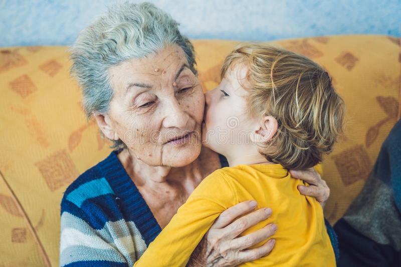 Portrait of a Happy Boy Kissing Happy Grandmother royalty free stock photography