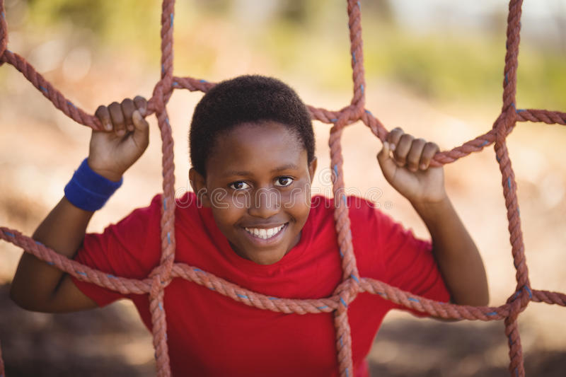 Portrait of happy boy leaning on net during obstacle course royalty free stock image