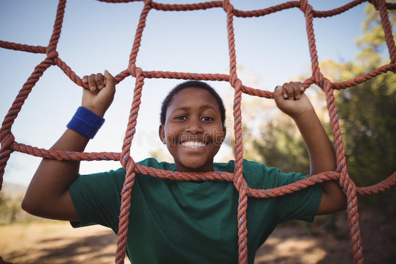 Portrait of happy boy leaning on net during obstacle course royalty free stock photography