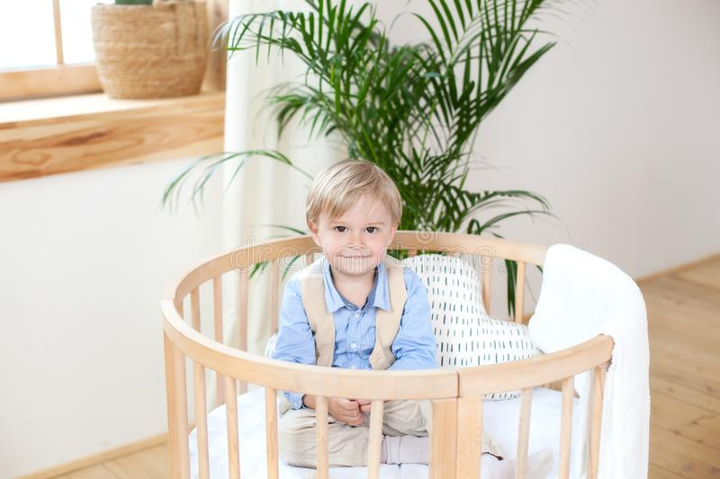 Portrait of a happy boy playing in a baby cot. The boy sits alone in a crib in the nursery. The lonely child stays in the crib. Lo. Neliness. The baby in bed is royalty free stock photos