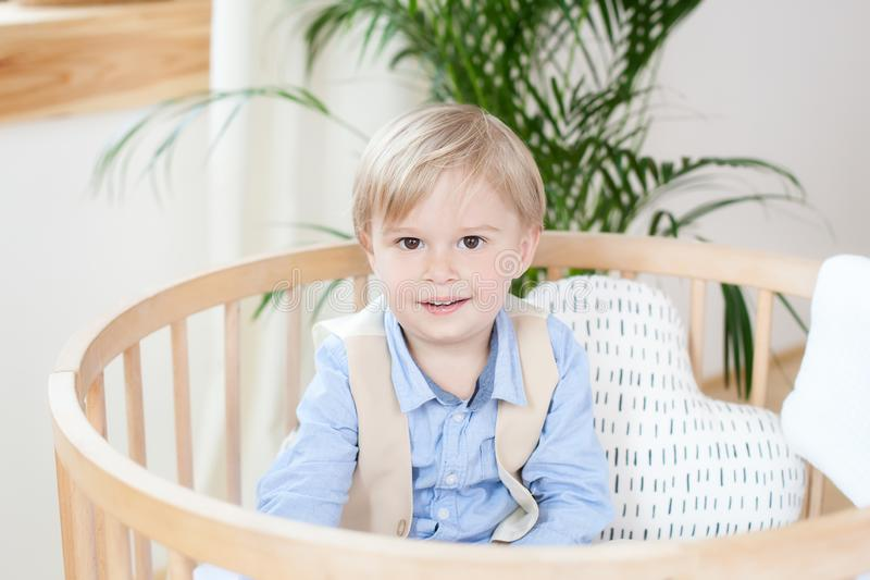 Portrait of a happy boy playing in a baby cot. The boy sits alone in a crib in the nursery. The lonely child stays in the crib. Lo. Neliness. The baby in bed is royalty free stock image