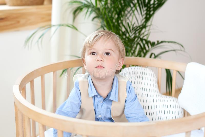 Portrait of a happy boy playing in a baby cot. The boy sits alone in a crib in the nursery. The lonely child stays in the crib. Lo royalty free stock photos