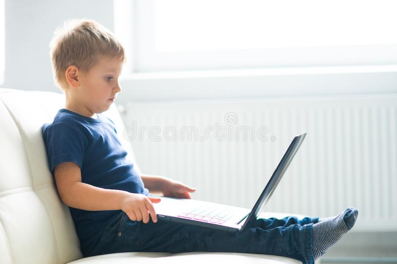 Portrait of happy boy playing with computer. Attractive kid with a laptop at home. Entertainment technology, futuristic royalty free stock photography
