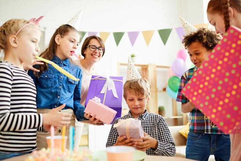 Gifts at Birthday Party. Portrait of happy boy receiving gifts surrounded by friends during Birthday party, copy space stock photo
