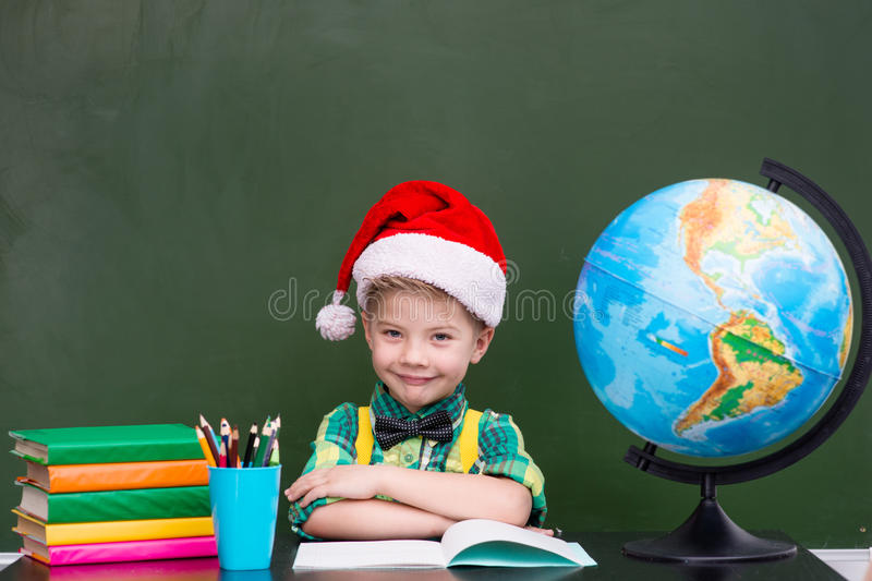 portrait of a happy boy with red christmas hat in classroom stock photos