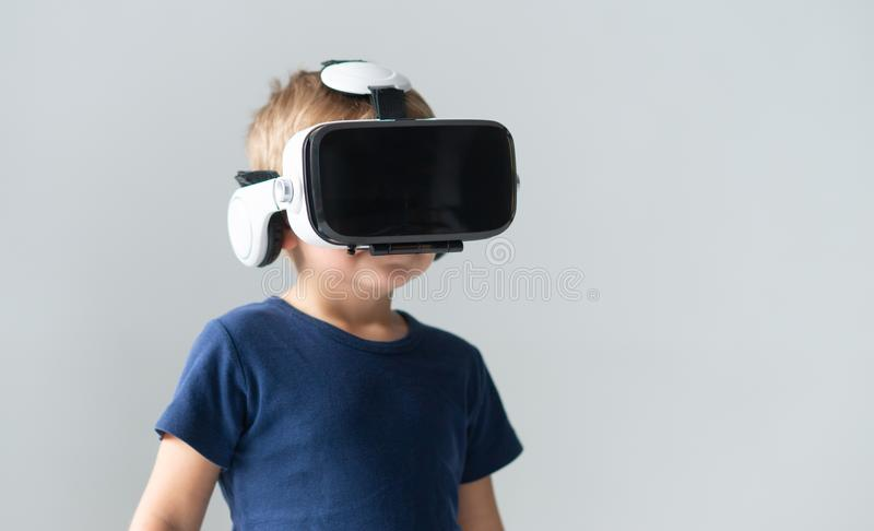 Portrait of happy boy in a virtual reality headset. Attractive kid using vr goggles at home. Entertainment technology royalty free stock photos