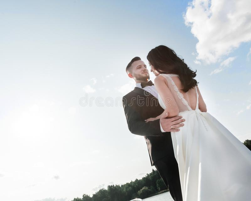 Portrait of happy bride and groom against the summer sky. Photo with copy space royalty free stock images