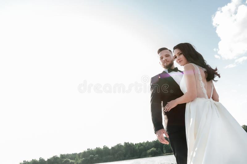 Portrait of happy bride and groom against the summer sky. Photo with copy space royalty free stock photo