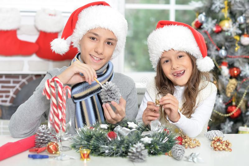 Happy brother and sister in Santa hats preparing for Christmas. Portrait of happy brother and sister in Santa hats preparing for Christmas stock image