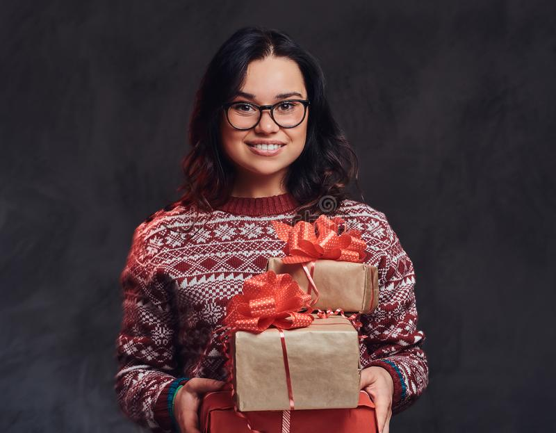 Portrait of a happy brunette girl wearing eyeglasses and warm sweater holding a gifts boxes, isolated on a dark textured royalty free stock images