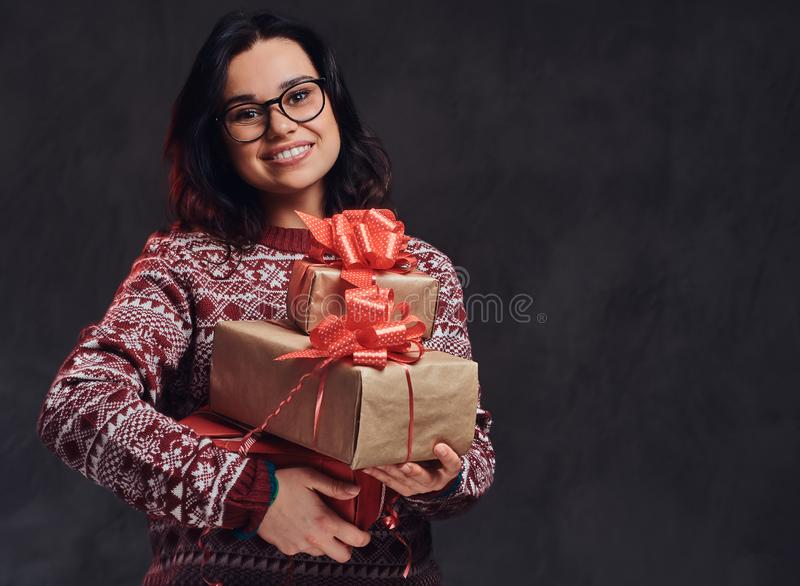 Portrait of a happy brunette girl wearing eyeglasses and warm sweater holding a gifts boxes, isolated on a dark textured royalty free stock photos