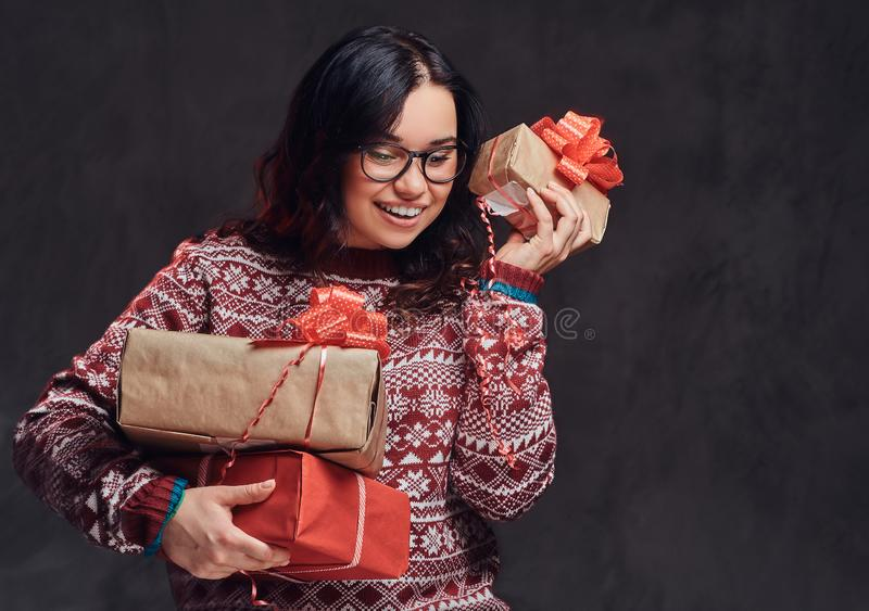 Portrait of a happy brunette girl wearing eyeglasses and warm sweater holding a gifts boxes, isolated on a dark textured royalty free stock photo