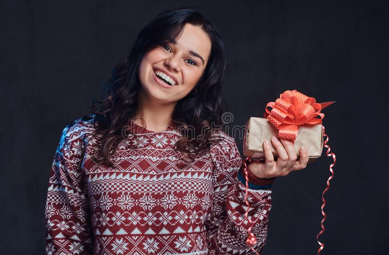 Portrait of a happy brunette girl wearing a warm sweater holding a gift box, isolated on a dark textured background. royalty free stock image
