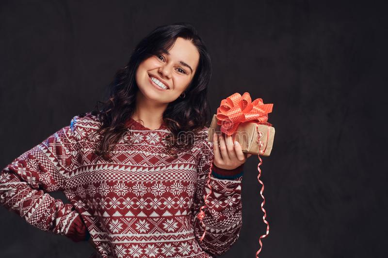 Portrait of a happy brunette girl wearing a warm sweater holding a gift box, isolated on a dark textured background. royalty free stock images