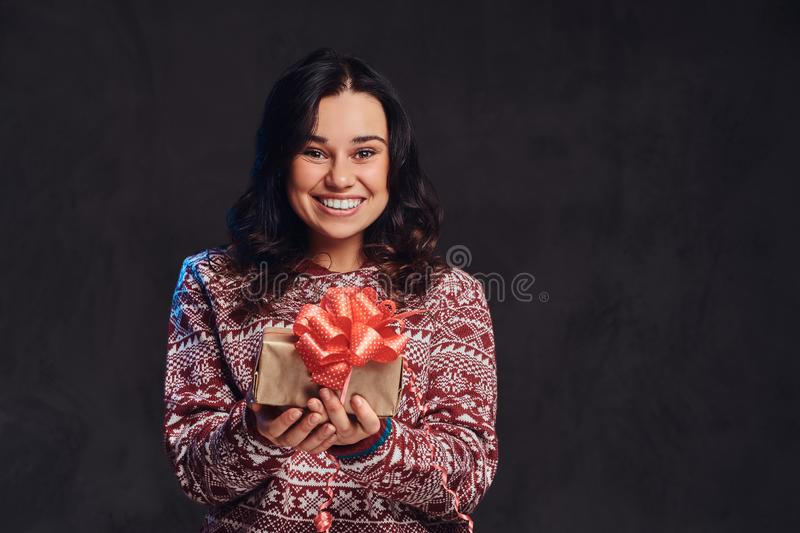 Portrait of a happy brunette girl wearing a warm sweater holding a gift box, isolated on a dark textured background. royalty free stock photos
