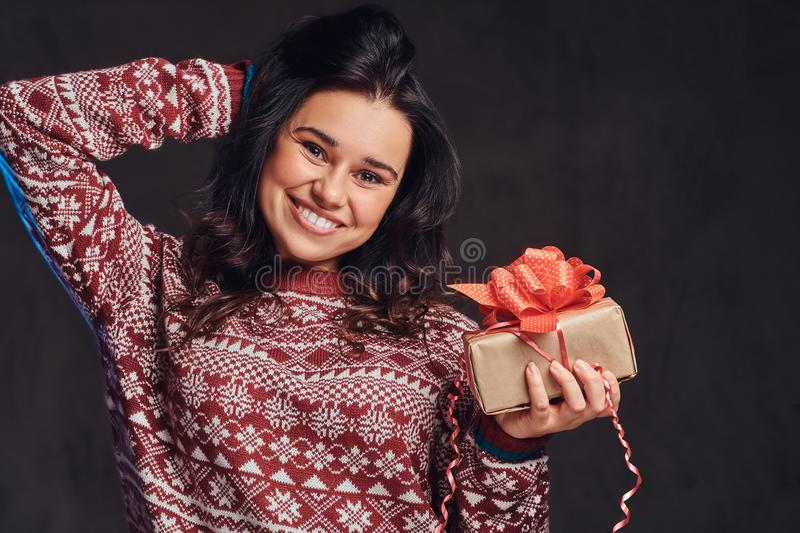 Portrait of a happy brunette girl wearing a warm sweater holding a gift box, isolated on a dark textured background. royalty free stock photography