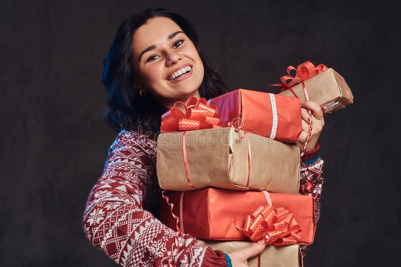 Portrait of a happy brunette girl wearing a warm sweater holding a gifts boxes, isolated on a dark textured background. stock photos