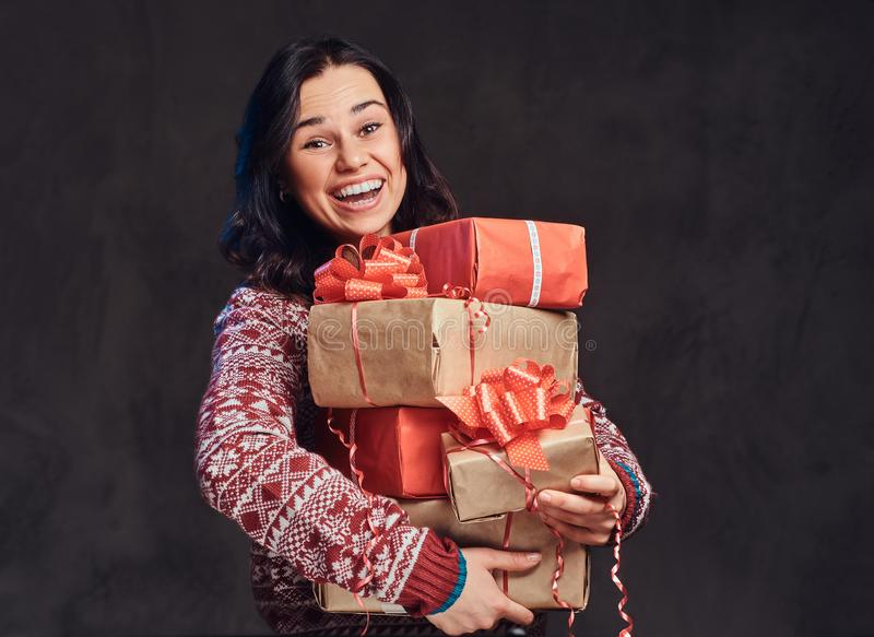 Portrait of a happy brunette girl wearing a warm sweater holding a gifts boxes, isolated on a dark textured background. stock photo