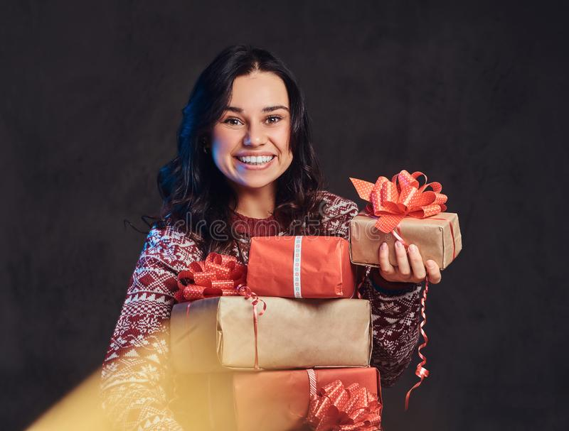 Portrait of a happy brunette girl wearing a warm sweater holding a gifts boxes, isolated on a dark textured background. stock photography