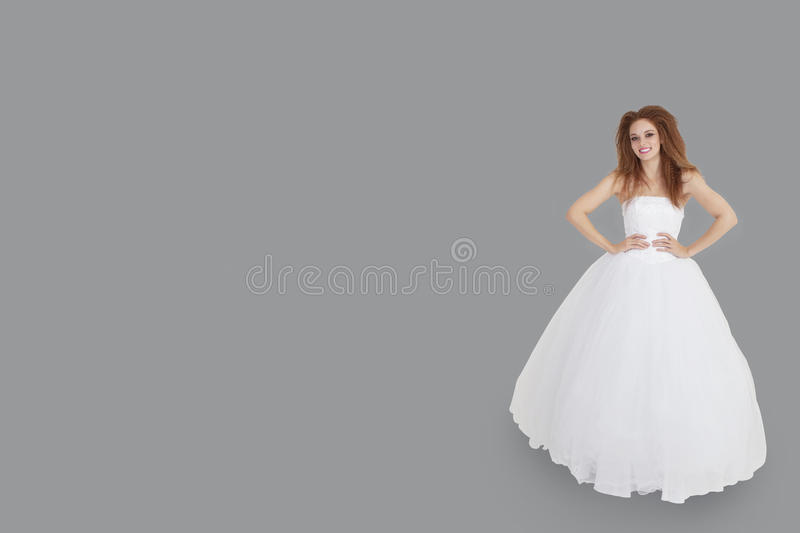 Download Portrait Of Happy Brunette In Wedding Dress With Hands On Hips Standing Over Gray Background Stock Image - Image: 29673175