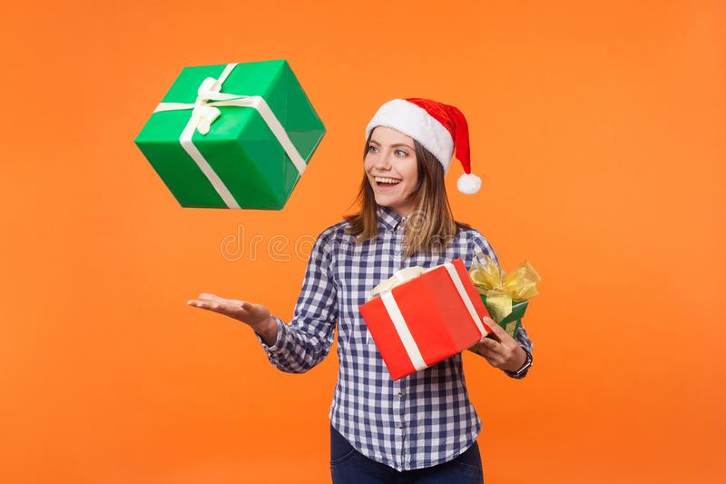 Portrait of happy brunette young woman in santa hat and checkered shirt standing throwing gift boxes in air or catching presents, stock images