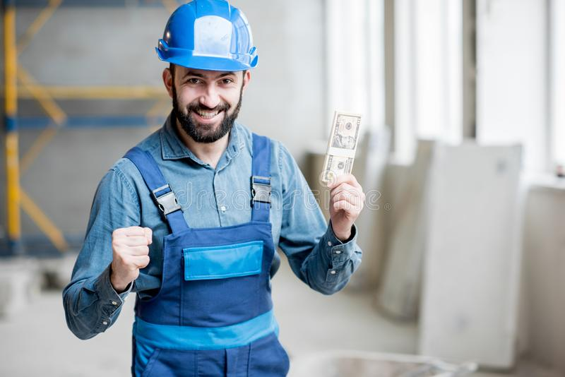 Builder with salary at the construction site royalty free stock photos