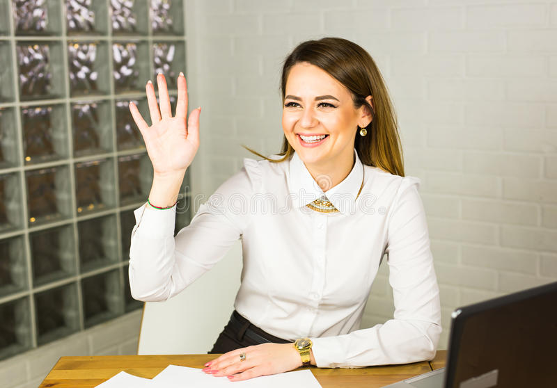 Portrait of a happy busiensswoman sitting at her workplace in office.  royalty free stock images